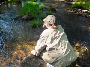 Natalia ponders the crystalline waters of the deep forest brook.