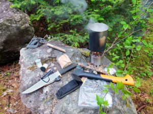 It's not so hard to set up a kitchen at camp.  A good knife to do the cutting, a little spice from the forest's bounty and a dash of salt, a light little wood stove and pot to cook in, and a hatchet to keep a steady flow of twigs for the stove.  Easy as boiling eggs!